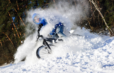 Cyclist extreme riding mountain bike in snow forest