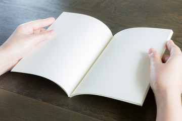 Hands open book on wood table