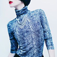 Sensual brunette model in fashionable blouse with snake print on