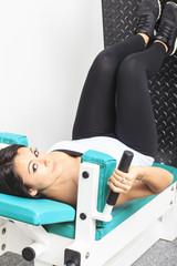 junge Frau an einem Sportgerät in einem Fitness Studio