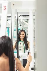 lächelnde Frau an einem Sportgerät im Fitness-Studio
