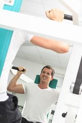 Mann an einem Sportgerät in einem Fitness-Studio