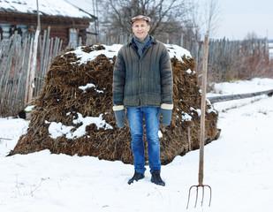 farmer in heap of fertilizer