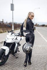 sexy blond woman in leather jacket,posing on motorbike