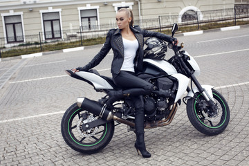 sexy girl with blond hair in leather jacket,posing on motorbike
