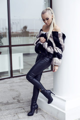 sexy beautiful blond woman wearing luxurious fur coat