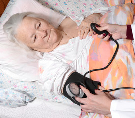 Female doctor measuring blood pressure of old woman