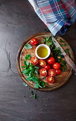 Ingredients for a tomato salad on a chopping board
