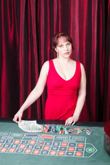 sexy girl wearing red dress with dollars in a casino