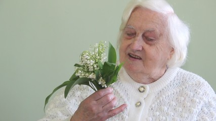 Old woman smelling flowers lily of the valley