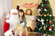 Santa Claus with little cute girl near Christmas tree at home
