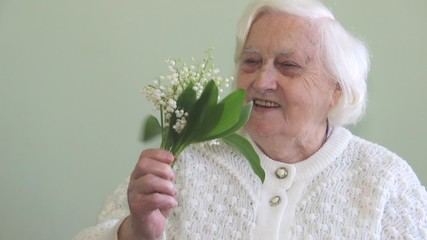 An old woman is receiving flowers
