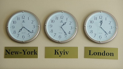 Three clocks showing the time zones of New York, London and Kyiv