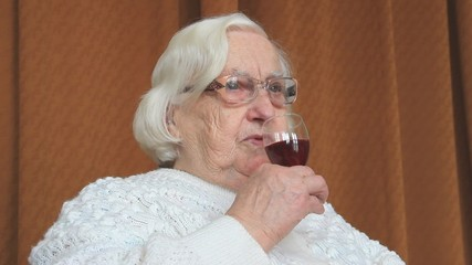An old woman is drinking red wine
