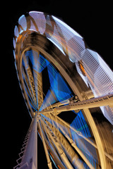 Fairground ferris wheel with colorful light trails