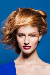 Portrait of lovely young model with beautiful hairstyle. on blue