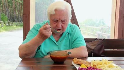 Elderly woman eats hot tomato soup.