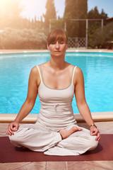 Frau praktiziert Yoga am Pool