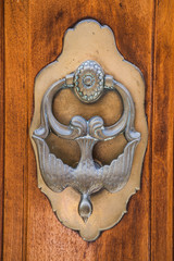 Old iron knocker on an old metal door in the Spain