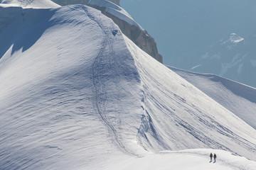 Mont Blanc mountaneers walking on snowy ridge.