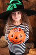 Little witch girl in hat asks candy