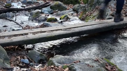 Hiking boots, hiker goes on a Board over stream.