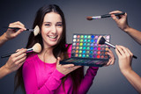 Cute make-up artist holding her vast palette of colors and hands poster