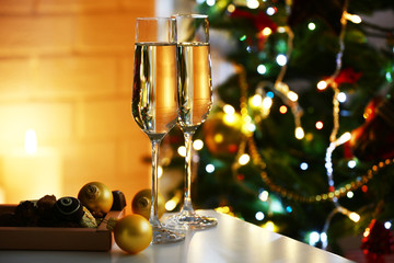 Two glass with champagne with chocolates and baubles