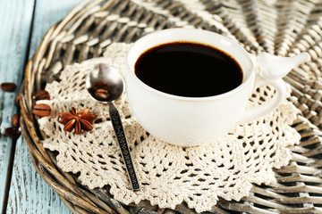 Cup of coffee with lace doily, spoon and coffee beans