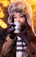 Asiatin trinkt Glühwein auf dem Weihnachtsmarkt
