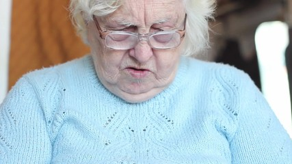 Old woman knitting socks. Tilt down shot with face expression