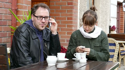Couple sitting in cafe and talking on a mobile phones