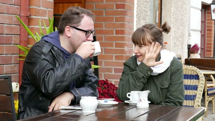 Two young,  smiling and happy people  have a chat in the cafe