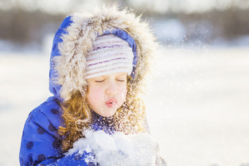 Little girl blows snow with mittens, on a snowflakes bokeh backg