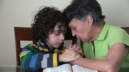 Family,two generations praying in a Christian daily devotional