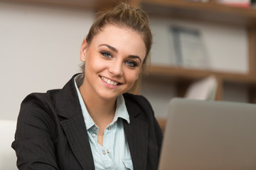 Happy Female Student In Library With Laptop
