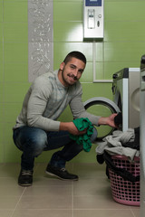 Young Man Loading The Washing Machine In Room