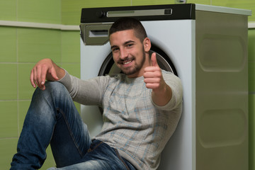Young Man Doing Housework Laundry Thumbs Up Sign