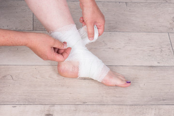 wrapping an ankle in a bandage