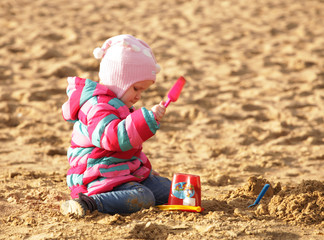 girl playing with sand at the autumn beach