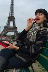Young caucasian woman enjoys macaroons in Paris