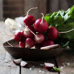 Fresh radish and salt on the wooden table, selective focus