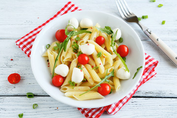 Penne with slices of cheese and tomatoes