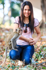 Tourist and monkey (Crab-eating macaque) in the park of Thailand