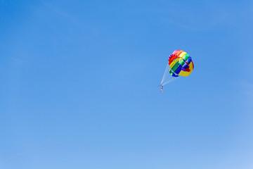 people against the sky, flying with a parachute