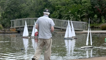 People sail remote control sailing wooden yachts in a pond