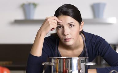 Unmotivierte Hausfrau lehnt auf dem Herd