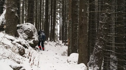 Hiker on slippery mountain trail during winter