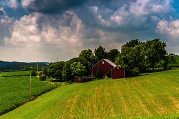 Dark clouds over a barn and farm fields in rural Southern York C