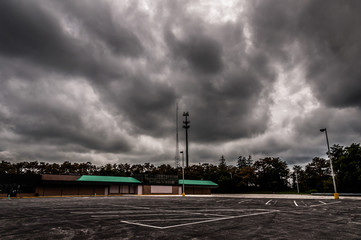 Dark storm clouds over an abandoned shopping center and parking